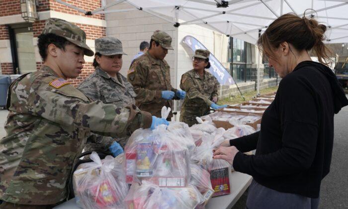 Tropas de la Guardia Nacional dan comida a residentes de New Rochelle en el condado Westchester, NY, el 12 de marzo de 2020. (Timothy A. Clary/AFP via Getty Images)