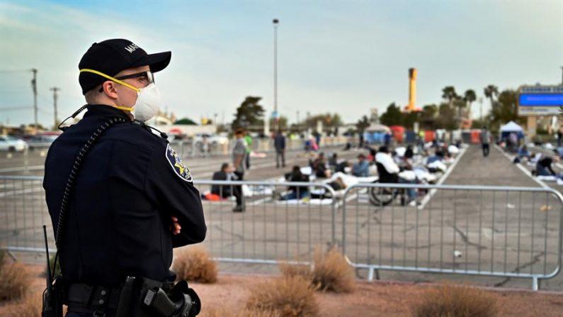 Un oficial de policía estadounidense vigila un refugio temporal para indigentes instalado en un aparcamiento del Centro Cashman en medio de la pandemia de coronavirus en EE.UU.. EFE/EPA/David Becker