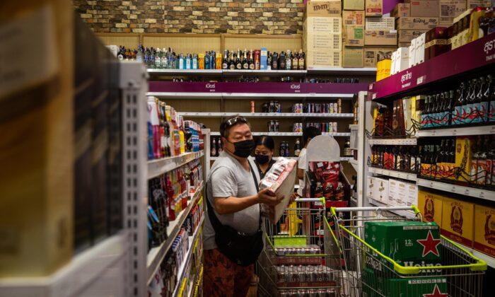 Personas con mascarillas compran cajas de cerveza en una tienda de comestibles en Bangkok, Tailandia, el 9 de abril de 2020. (Lauren DeCicca/Getty Images)