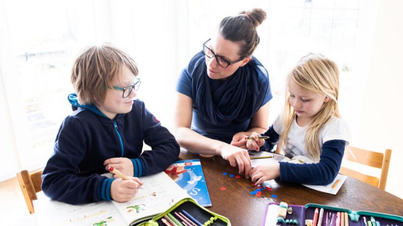 Una mamá ayuda a su hijo de nueve años y a su hija de seis a hacer los deberes de la escuela el 15 de marzo de 2020 en Dinslaken, Alemania. (Lars Baron/Getty Images)