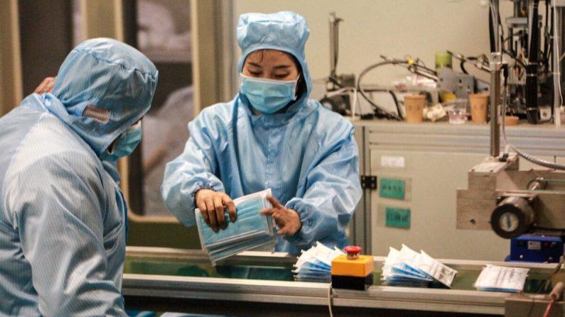Trabajadores producen máscaras faciales en una fábrica en Yangzhou, en la provincia oriental china de Jiangsu, el 26 de enero de 2020. (STR/AFP a través de Getty Images)