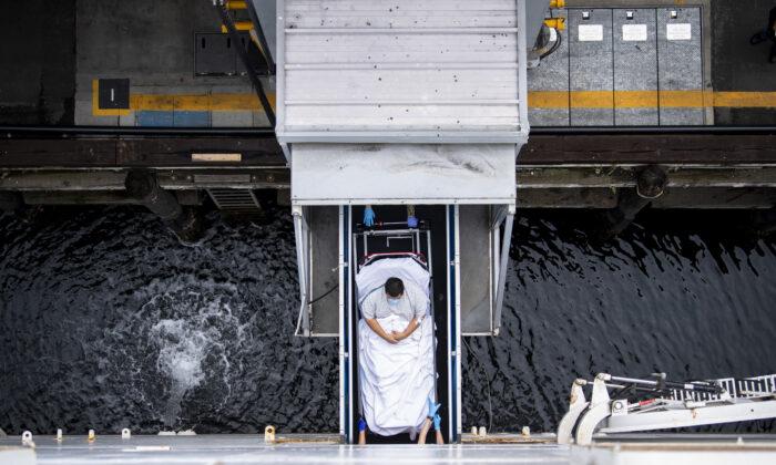 Foto de archivo publicada por la Marina de Estados Unidos, los marineros transportan a un paciente para ser admitido a bordo del buque hospital USNS Mercy (T-AH 19) en Los Ángeles, California el 6 de abril de 2020. (Ryan Breeden/Marina de EE.UU. vía Getty Images)