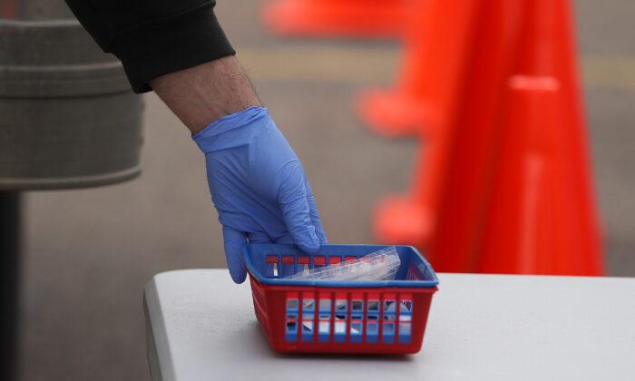 Un cliente recoge un kit de hisopado en un sitio de pruebas de autoservicio de Rite Aid en Macomb, Michigan, el 21 de abril de 2020. (Gregory Shamus/Getty Images)