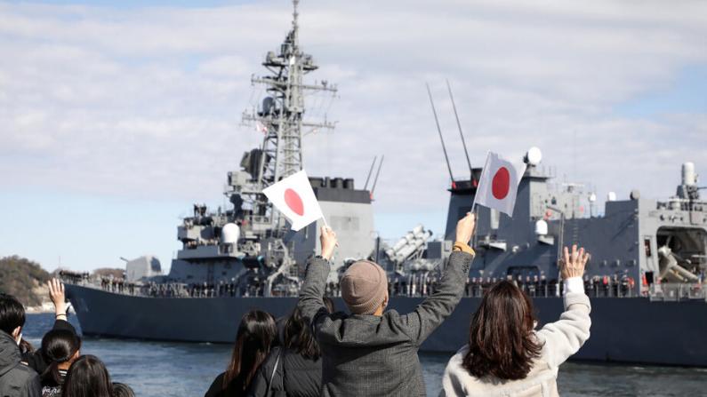 """Personas saludan mientras el destructor de la Fuerza de Autodefensa Marítima de Japón """"Takanami"""" parte hacia el Medio Oriente en la base naval de Yokosuka en Yokosuka, prefectura de Kanagawa, el 2 de febrero de 2020. (Foto de STR / JIJI PRESS / AFP vía Getty Images)"""