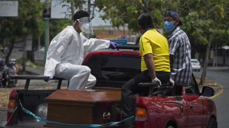 Tres personas viajan sobre una camioneta que traslada un ataúd hacia un cementerio, este jueves en Managua (Nicaragua). EFE/Jorge Torres