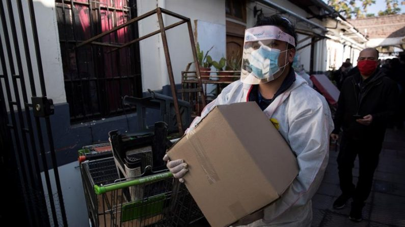 Un trabajador municipal carga una caja con alimentos para entregar a una familia para pasar la cuarentena por la COVID-19, el 21 de mayo de 2020 en Santiago (Chile). EFE/ Alberto Valdés
