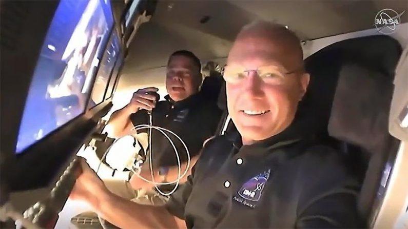 Una imagen fija tomada en vídeo y distribuida por la NASA el 31 de mayo de 2020 muestra a los astronautas de la NASA Doug Hurley (en primer plano) y Bob Behnken pidiendo a los controladores de la misión un informe sobre su segundo día de vuelo a bordo de la nave espacial SpaceX Crew Dragon en la misión SpaceX Demo-2 de la NASA, aproximándose al acoplamiento con la Estación Espacial Internacional (ISS), el 31 de mayo de 2020. (TV DE LA NASA EFE, EPA y la NASA)
