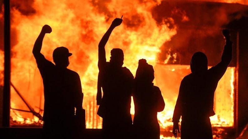 Manifestantes alzan el puño junto a una tienda en llamas, durante los disturbios provocados tras la muerte del afroamericano George Floyd a manos de la policía, en Mineápolis, Minnesota, Estados Unidos. (EFE/Craig Lassig)