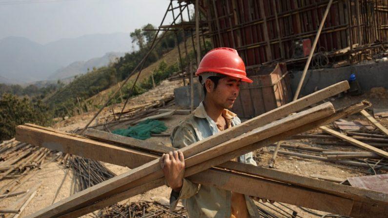 "Un trabajador chino transporta materiales para la primera línea de ferrocarril que une China con Laos, una parte clave del proyecto ""La Franja y La Ruta"" de Beijing a través del Mekong, en Luang Prabang, el 8 de febrero de 2020. (AIDAN JONES/AFP a través de Getty Images)"