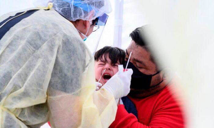 José Vatres (derecha) sostiene a su hijo Aidin mientras el practicante de enfermería Alexander Panis realiza el test de COVID-19 en una estación móvil de pruebas en el área de estacionamiento de una escuela pública en Compton, California, el 28 de abril de 2020. (Robyn Beck/AFP vía Getty Images)