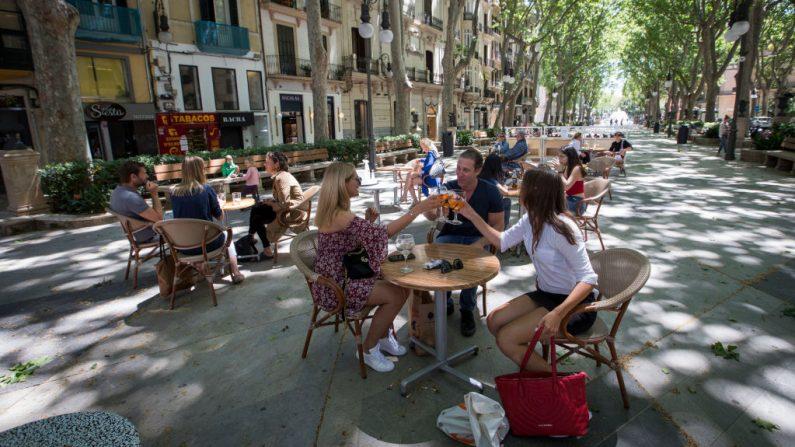 La gente comparte un brindis en un bar de la terraza en Palma de Mallorca el 11 de mayo de 2020, mientras España avanzaba hacia la relajación de su estricto bloqueo en ciertas regiones. (JAIME REINA / AFP vía Getty Images)