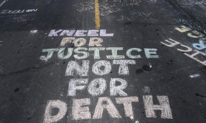 """La frase """"Inclínate por la justicia, no por la muerte"""" apareció escrita en la calle colindante al Cup Foods donde George Floyd fue asesinado bajo custodia policial en Minneapolis, Minn., el 28 de mayo de 2020. (Stephen Maturen/Getty Images)"""