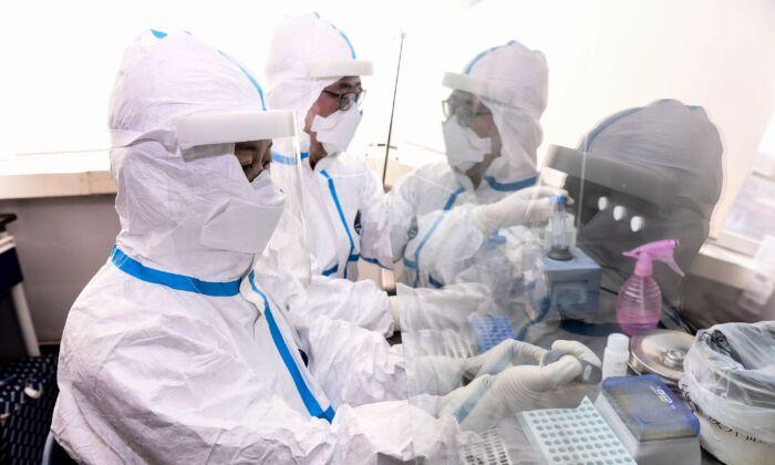 Los técnicos de laboratorio trabajan en el análisis de muestras de personas que serán analizadas para detectar el virus del PCCh en un laboratorio en Shenyang, China, el 12 de febrero de 2020. (STR/AFP vía Getty Images)