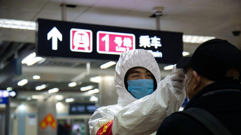 Un trabajador de la salud comprueba la temperatura de un hombre que entra en el metro el 26 de enero de 2020 en Beijing, China. (Betsy Joles/Getty Images)