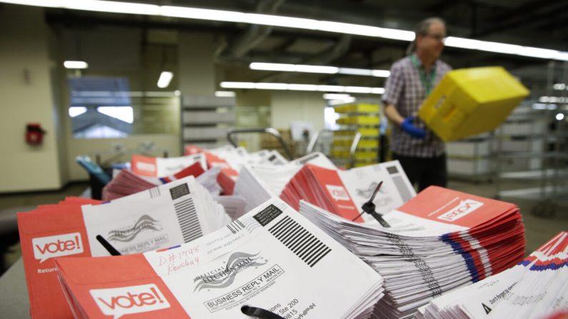 Los sobres vacíos de las papeletas abiertas de voto por correo para las primarias presidenciales se apilan en una mesa en las elecciones del condado de King en Renton, Washington, el 10 de marzo de 2020. (Jason Redmond/AFP vía Getty Images)