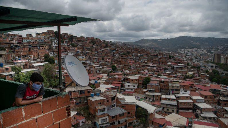 CARACAS, VENEZUELA - MARZO 23: Una persona con una máscara protectora mira el barrio bajo de Petare el 23 de marzo de 2020 en Caracas, Venezuela. (Foto de Carlos Becerra/Getty Images)