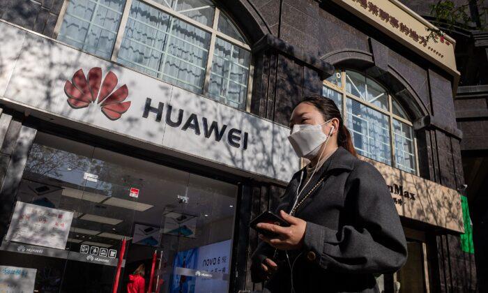 Una mujer con una máscara facial en medio de las preocupaciones por el coronavirus COVID-19 camina sosteniendo su smartphone frente a una tienda Huawei en una calle de Beijing el 22 de abril de 2020. (NICOLAS ASFOURI/AFP vía Getty Images)