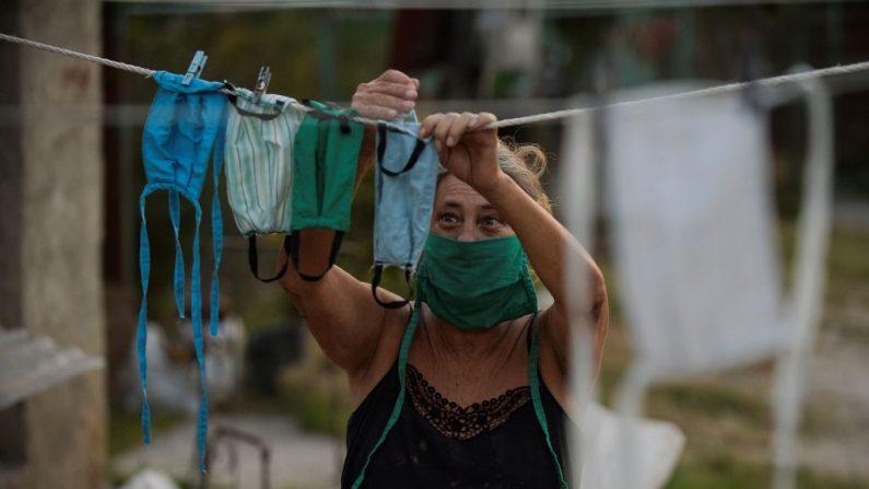Una mujer cuelga mascarillas faciales después de lavarlas en su casa en el municipio de Mariel en Artemisa, Cuba, el 23 de abril de 2020. (YAMIL LAGE/AFP vía Getty Images)