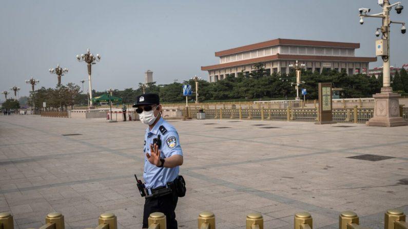 Un agente de policía gesticula mientras asegura un área en los alrededores de la Plaza Tiananmen durante el Día Mundial de la Libertad de Prensa en Beijing, China, el 3 de mayo de 2020. (NICOLAS ASFOURI/AFP a través de Getty Images)