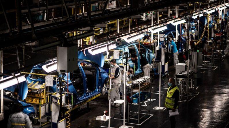 Empleados con máscaras de protección contra la propagación del COVID-19 trabajan a lo largo de la línea de montaje que produce tanto el vehículo eléctrico Renault Zoe como el vehículo híbrido Nissan Micra, en Flins-sur-Seine, Francia, el 6 de mayo de 2020. (MARTIN BUREAU/AFP vía Getty Images)