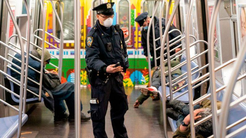 La policía de la ciudad de Nueva York despeja los vagones de pasajeros en la última parada de la estación de Coney Island en Brooklyn, Nueva York, el 6 de mayo de 2020. (COREY SIPKIN/AFP vía Getty Images)