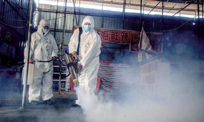 Dos voluntarios están rociando desinfectante en un mercado en la ciudad fronteriza de Suifenhe, en la provincia de Heilongjiang, noreste de China, el 6 de mayo de 2020. (STR/AFP a través de Getty Images)