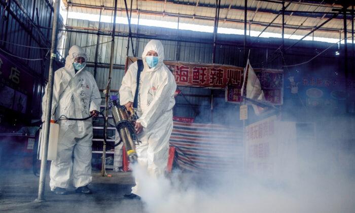 Esta foto, tomada el 6 de mayo de 2020, muestra a voluntarios rociando desinfectante en un mercado, como medida preventiva contra el coronavirus COVID-19, en Suifenhe, provincia de Heilongjiang, China. (STR/AFP a través de Getty Images)