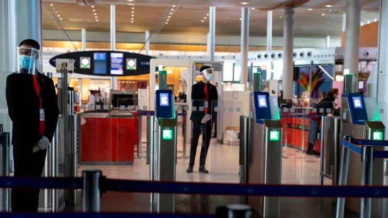El personal del aeropuerto Charles de Gaulle lleva máscaras y viseras de protección en la Terminal 2 del aeropuerto internacional Charles de Gaulle en Roissy, cerca de París (Francia), el 14 de mayo de 2020. (Ian LANGSDON / EPA POOL / AFP a través de Getty Images)