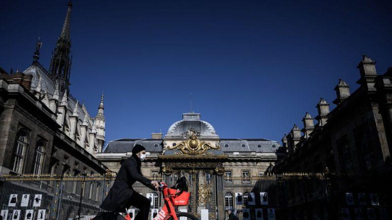 Un hombre pasa en bicicleta frente al histórico Palacio de Justicia situado en la Île de la Cité de París, el 15 de mayo de 2020, durante un levantamiento parcial de las restricciones debido a que la pandemia Covid-19 causada por el nuevo coronavirus. (PHILIPPE LOPEZ/AFP vía Getty Images)