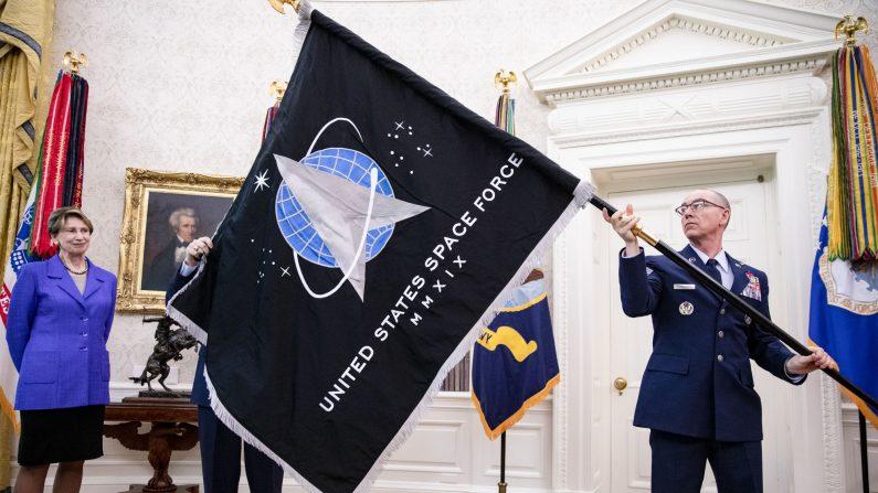 El General Jay Raymond (derecha), Jefe de Operaciones Espaciales, y el sargento Roger Towberman (izquierda), con la Secretaria de la Fuerza Aérea Barbara Barrett presentan al Presidente de los Estados Unidos, Donald Trump, la bandera oficial de la Fuerza Espacial de los Estados Unidos en la Oficina Oval Casa Blanca en Washington, DC, el 15 de mayo de 2020. (Samuel Corum-Pool/Getty Images)