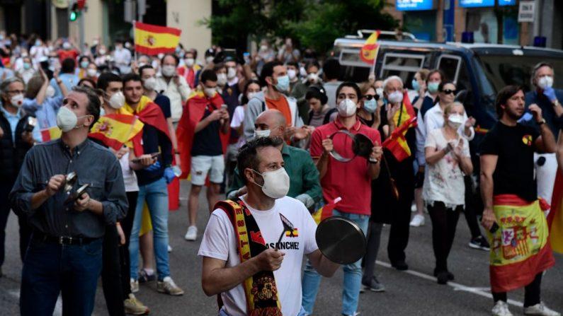 La gente golpea ollas durante una protesta contra el gobierno por su gestión de la crisis del virus del PCCh frente a la sede del gobernante Partido Socialista en Madrid (España) el 18 de mayo de 2020, a pesar del cierre nacional para evitar la propagación de la enfermedad COVID-19. (JAVIER SORIANO/AFP vía Getty Images)