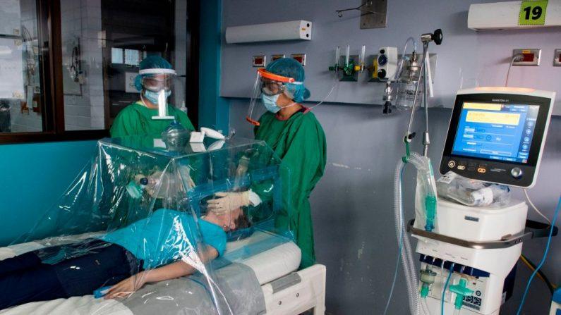 """El personal de salud demuestra con una enfermera cómo atender a un paciente utilizando una cápsula como protección tanto para el paciente como para el personal médico, fabricada en el Instituto Tecnológico de Costa Rica, también conocido como """"ITCR"""" o """"TEC"""", en Cartago (Costa Rica) el 8 de mayo de 2020, durante la pandemia de COVID-19. (EZEQUIEL BECERRA/AFP vía Getty Images)"""