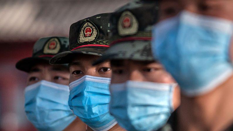 Agentes de la policía paramilitar con máscaras faciales marchan frente a la entrada de la Ciudad Prohibida en Beijing el 19 de mayo de 2020. (Nicolas Asfouri/AFP a través de Getty Images)