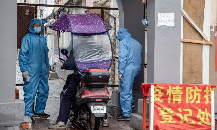 Voluntarios comprueban la identidad de un residente a la entrada de un complejo residencial en la ciudad de Jilin, China, el 22 de mayo de 2020. (STR/AFP vía Getty Images)