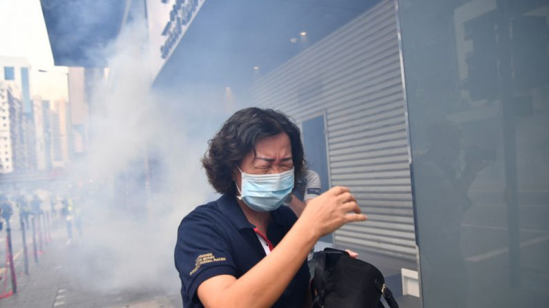 Una mujer reacciona después de que la policía antidisturbios disparara gas lacrimógeno para dispersar a los manifestantes que participaban en una manifestación prodemocracia contra una nueva ley de seguridad propuesta en Hong Kong el 24 de mayo de 2020. (Foto de ANTHONY WALLACE/AFP vía Getty Images)