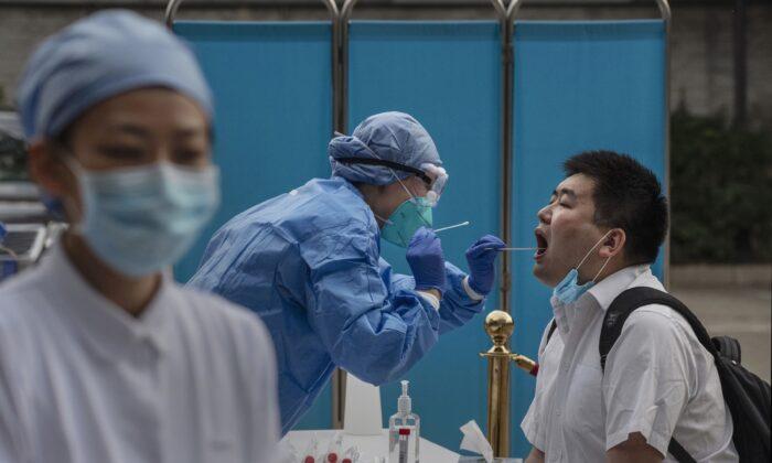Un trabajador sanitario chino realiza una prueba de ácido nucleico a un periodista que cubre los acontecimientos en torno al Congreso Nacional del Pueblo en Beijing, China, el 28 de mayo de 2020. (Kevin Frayer/Getty Images)