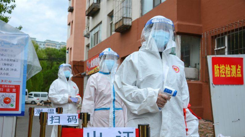 Personal espera para verificar el permiso de entrada de las personas, controlar su temperatura corporal y escanear sus códigos de salud en la entrada de un complejo residencial en la ciudad de Jilin, China, el 25 de mayo de 2020. (STR/AFP a través de Getty Images)