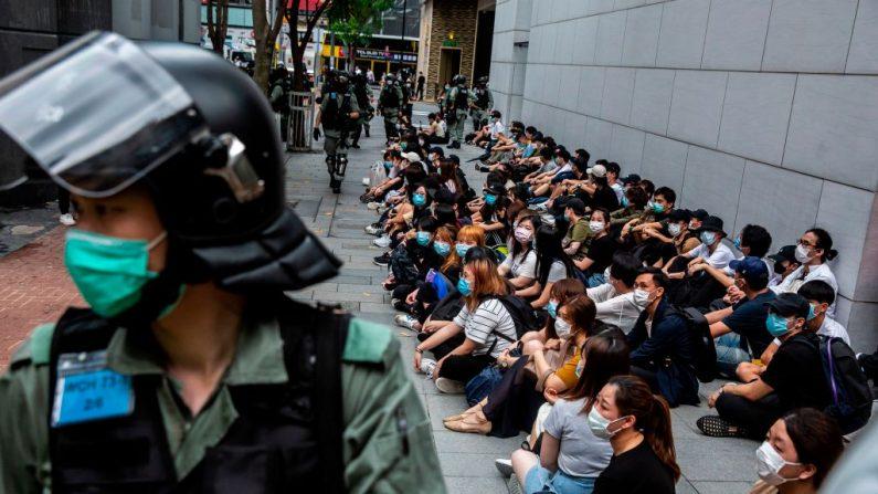 Policía antidisturbios detiene a un grupo de personas (D) durante una protesta en el distrito de Causeway Bay de Hong Kong el 27 de mayo de 2020, (ISAAC LAWRENCE/AFP vía Getty Images)
