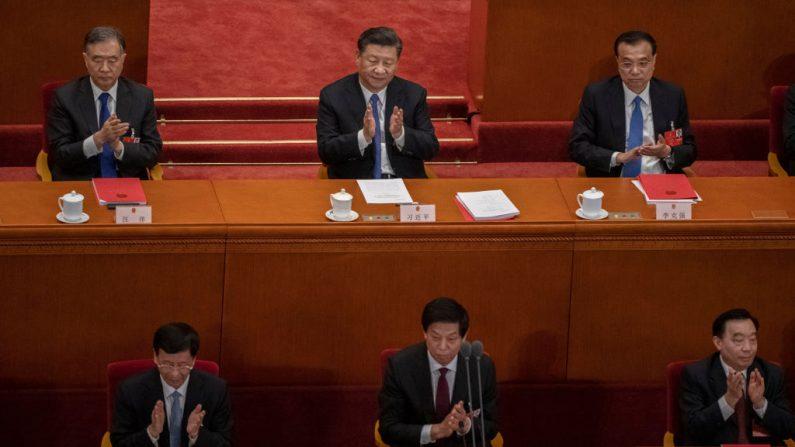 El mandatario chino Xi Jinping, en el centro, y el primer ministro Li Keqiang, en la parte superior derecha, y otros miembros del régimen comunista aplauden el resultado de la votación sobre un nuevo proyecto de ley de seguridad para Hong Kong durante la sesión de clausura de la Asamblea Popular Nacional el 28 de mayo de 2020 en Beijing, China. (Foto de Kevin Frayer/Getty Images)