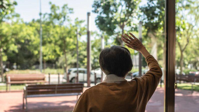 Carme Peris saluda con la mano detrás de la ventana de la residencia de ancianos La Mallola el 19 de mayo de 2020 en Esplugues del Llobregat, cerca de Barcelona, España. Muchos de los cientos de miles de residentes en las residencias de ancianos de España ya están en riesgo de soledad. (David Ramos/Getty Images)