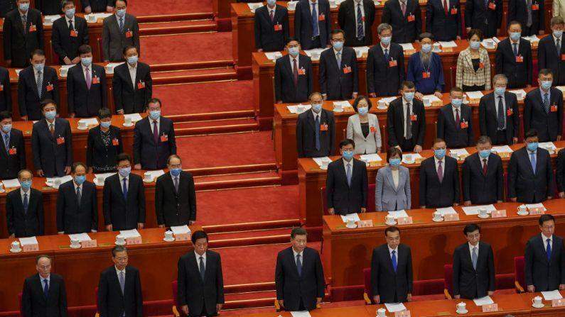 El líder chino Xi Jinping (C), el Primer Ministro chino Li Keqiang (R) y el miembro del Comité Permanente del Politburó Li Zhanshu (L) y otros asistentes se ponen de pie al comienzo de la Conferencia Política y Consultiva del Pueblo Chino el 21 de mayo de 2020 en el Gran Salón del Pueblo en Beijing, China.  (Andrea Verdelli/Getty Images)