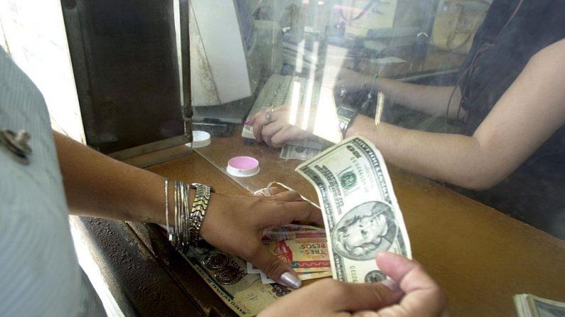 Una mujer intercambia dólares estadounidenses por pesos cubanos el 26 de octubre de 2004 en La Habana, Cuba. (Jorge Rey/Getty Images)