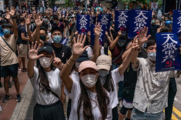 """Una manifestación en contra de la propuesta de Ley de Seguridad Nacional de Beijing en Hong Kong, el 24 de mayo de 2020. Los manifestantes levantan cinco dedos que simbolizan sus demandas y sostienen carteles que dicen """"El cielo está eliminando al PCCh"""". (Anthony Wallace/AFP a través de Getty Images)"""