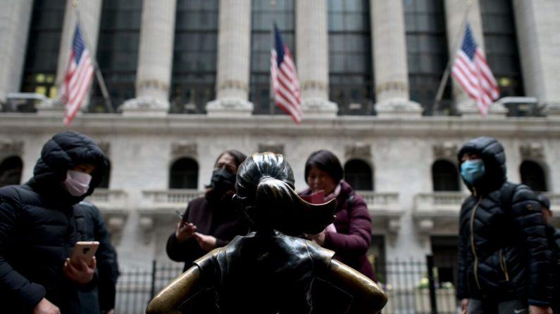Turistas chinos con mascarillas faciales se paran frente a la Bolsa de Nueva York en Wall Street en la ciudad de Nueva York, el 3 de febrero de 2020. (Johannes Eisele/AFP a través de Getty Images)