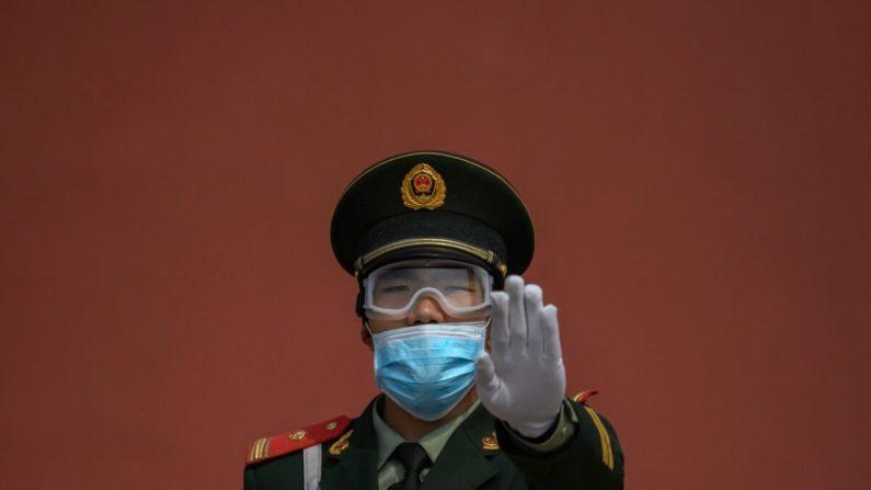 Un oficial de la policía paramilitar china hace un gesto mientras usa una mascarilla protectora mientras está de guardia en la entrada de la Ciudad Prohibida cuando se reabrió a visitantes limitados en Beijing, China, el 1 de mayo de 2020. (Kevin Frayer/Getty Images