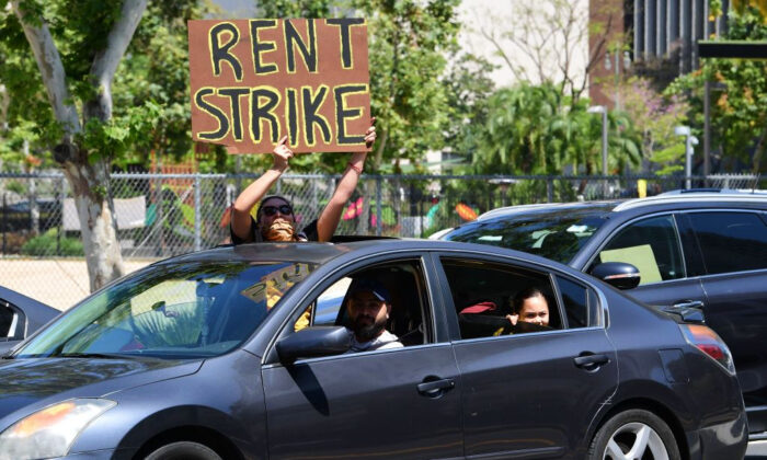 Los manifestantes convocan a una huelga de alquileres durante la pandemia de COVID-19 al pasar por el Ayuntamiento de Los Ángeles, California, el 1 de mayo de 2020. (Frederic J. Brown/AFP a través de Getty Images)