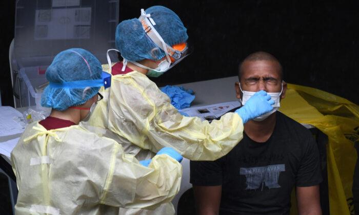 Un trabajador de la salud recoge una muestra de hisopo nasal para una prueba de COVID-19 en Singapur el 27 de abril de 2020. (Roslan Rahman/AFP/Getty Images)