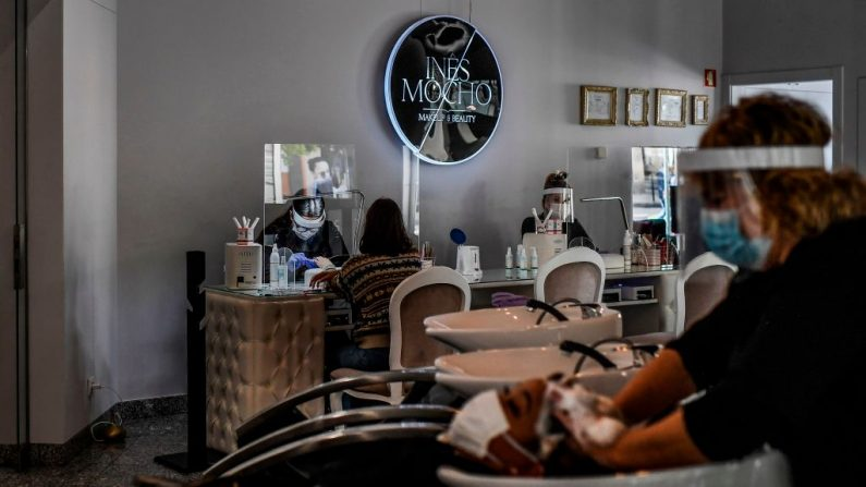 Estilistas con mascarillas faciales y escudos acrílicos atienden a clientes en un salón de belleza en Lisboa el 4 de mayo de 2020. (PATRICIA DE MELO MOREIRA/AFP vía Getty Images)