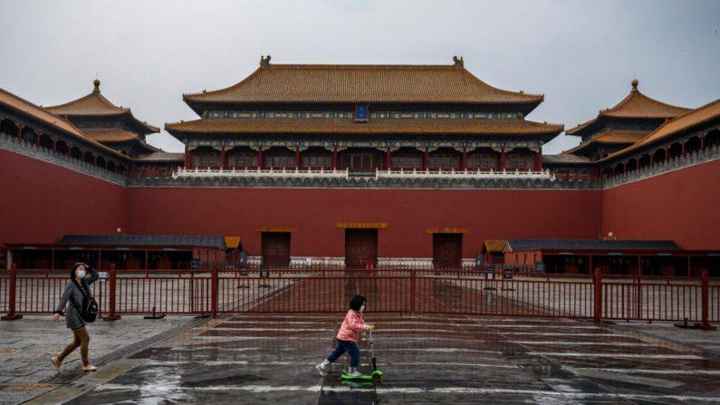 Una niña china con mascarilla protectora conduce su scooter fuera de la puerta de la Ciudad Prohibida, que permanece cerrada a los visitantes, en Beijing, China, el 19 de abril de 2020. (Kevin Frayer/Getty Images)