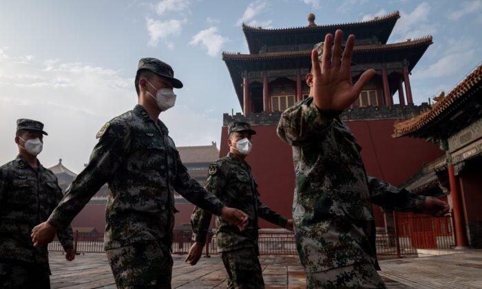 Soldados del Ejército Popular de Liberación de China marchan junto a la entrada de la Ciudad Prohibida durante la ceremonia de apertura de una reunión política en Beijing el 21 de mayo de 2020. (NICOLAS ASFOURI / AFP a través de Getty Images)